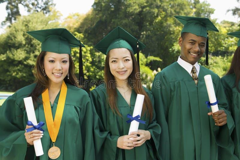 Graduates hoisting diplomas outside university royalty free stock photography