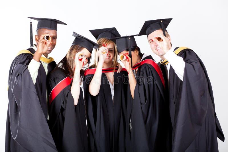 Graduates looking through diploma stock photos