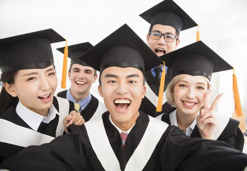Graduates making selfie photo in classroom. Happy graduates making selfie photo in classroom stock photo