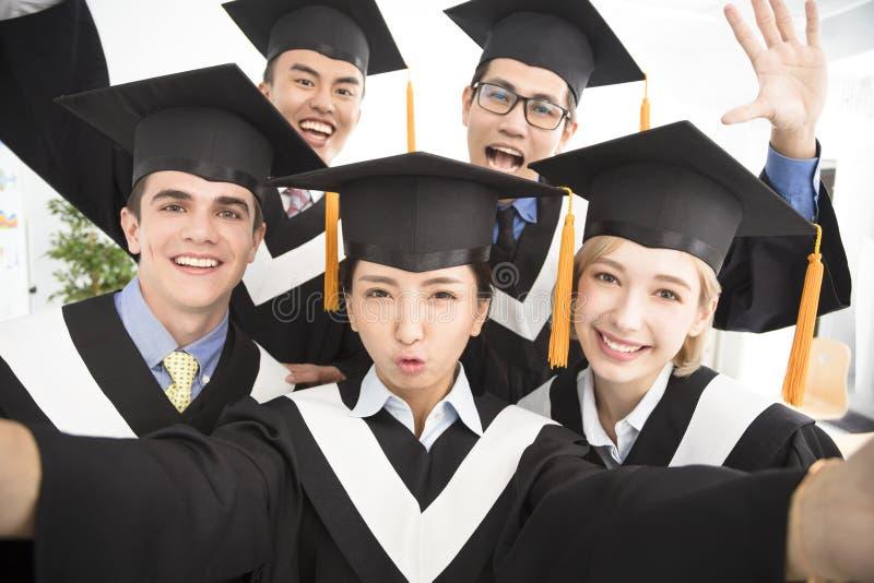 Graduates making selfie photo in classroom. Happy graduates making selfie photo in classroom royalty free stock photo