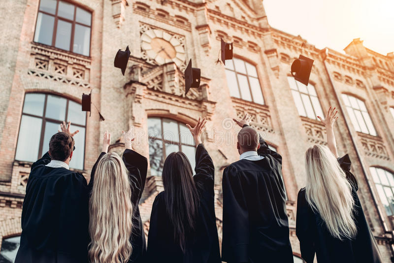 Graduates near university. Are throwing up hats in the air royalty free stock photography