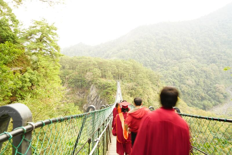 Graduates on suspension bridge stock photo