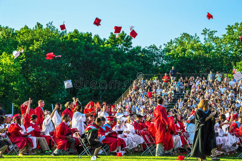 Graduates Toss Caps. MANALAPAN, NEW JERSEY/USA – JUNE 24: Manalapan High School students toss up their caps in celebration after they receive their stock photos