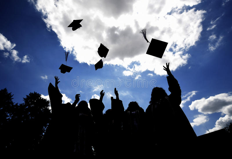 Graduates tossing hats. In the blue sky royalty free stock photography