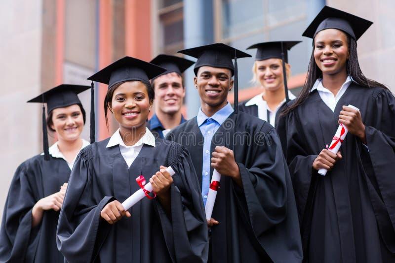 Graduates university building. Young graduates standing in front of university building on graduation day royalty free stock photo
