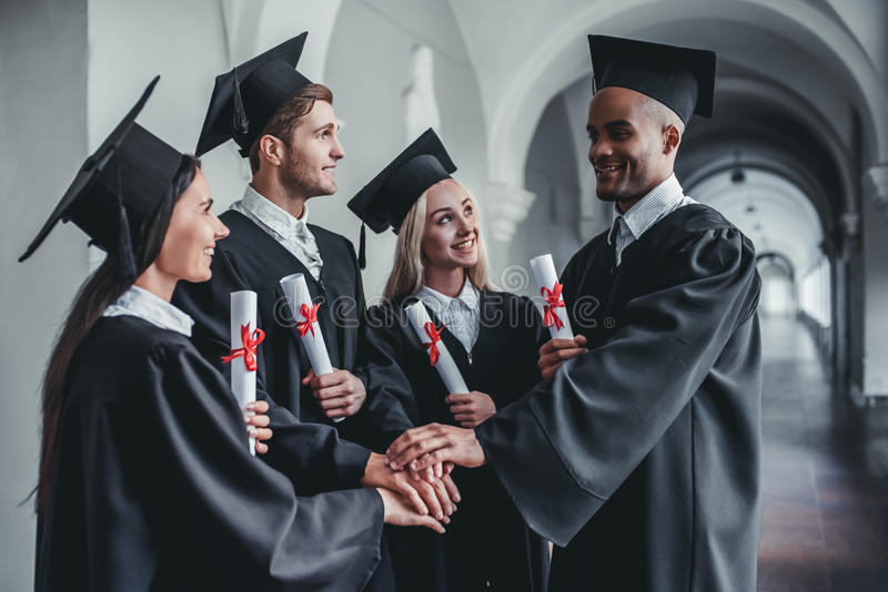 Graduates in university. Happy graduates are standing in university hall in mantles with diplomas in hand royalty free stock images