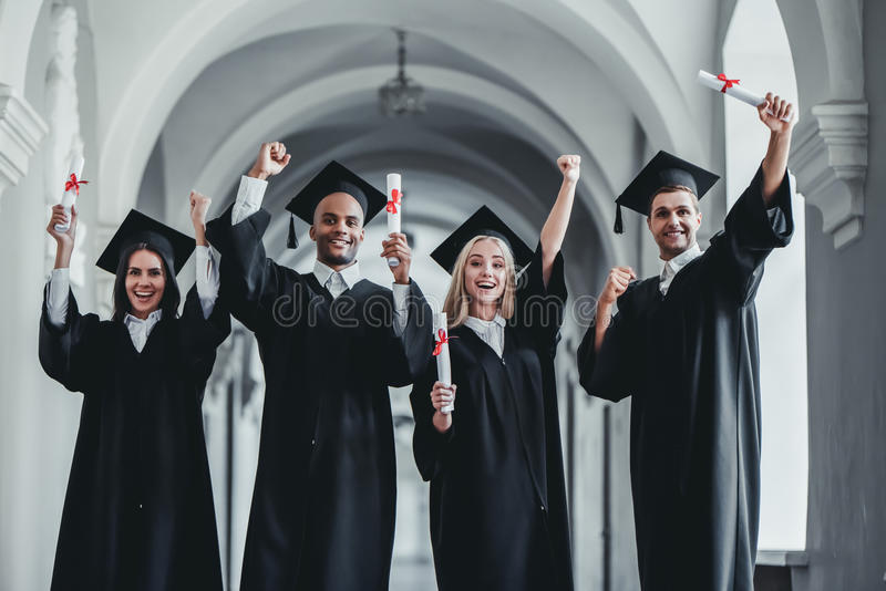 Graduates in university. Happy graduates are standing in university hall in mantles with diplomas in hand. Smiling and looking at the camera royalty free stock photos