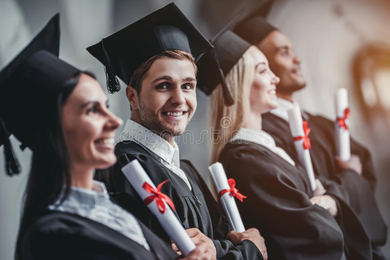 Graduates in university. Happy graduates are standing in row in university hall in mantles with diplomas in hand stock photos
