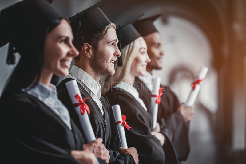 Graduates in university. Happy graduates are standing in a row in university hall in mantles with diplomas in hand royalty free stock photo