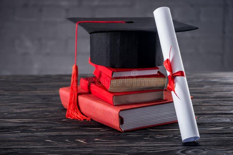 Graduatie GLB met diploma en boeken op lijst stock afbeelding