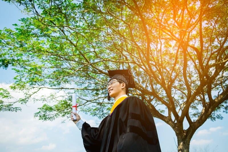 Graduatie: Student en de Graduatie die van de glimlachholding cer opstaan stock afbeelding