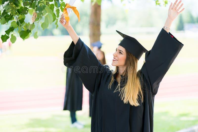 Graduatie: Student Standing With Diploma met erachter Vrienden stock fotografie