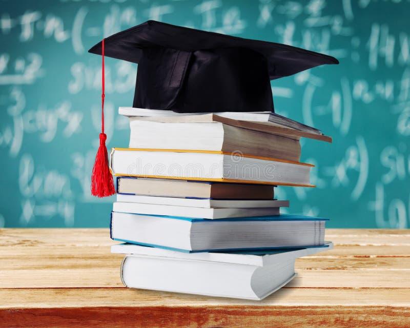 Graduatiebaret bovenop stapel boeken  stock afbeelding