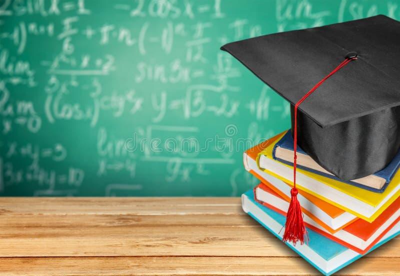 Graduatiehoed en stapel boeken op houten lijst stock afbeelding