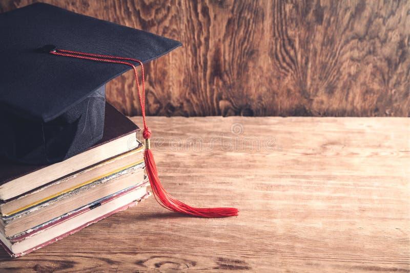 Graduatiehoed met boeken op lijst Het concept van het onderwijs stock afbeelding