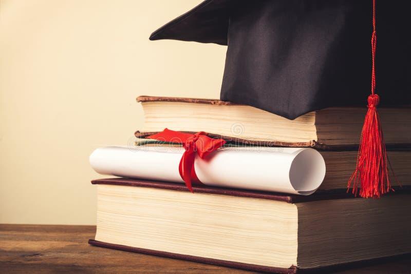 Graduatiehoed op stapel van boeken en diploma royalty-vrije stock foto's