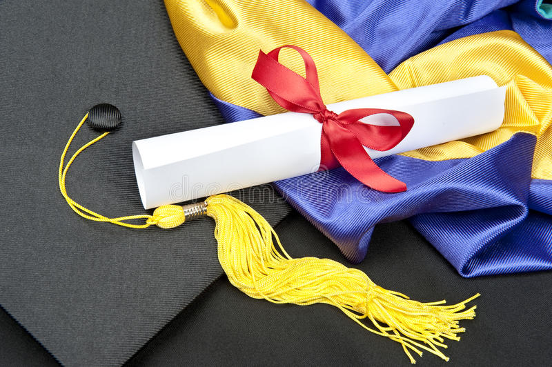 Graduation. Cap with tassel and rolled up diploma tied with a red ribbon stock photos