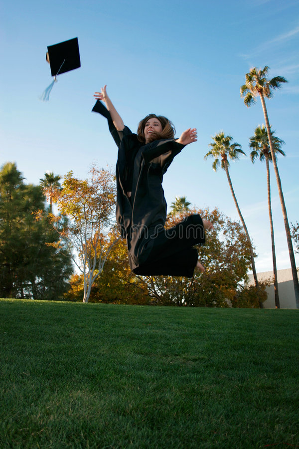 Graduation. Woman jumping for joy with her graduation gown and cap
