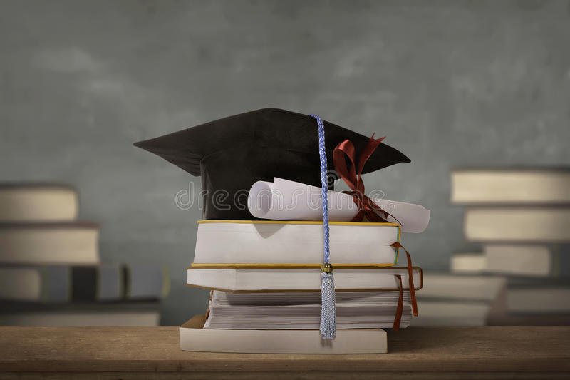 Graduation cap above stack books with degree paper royalty free stock photography