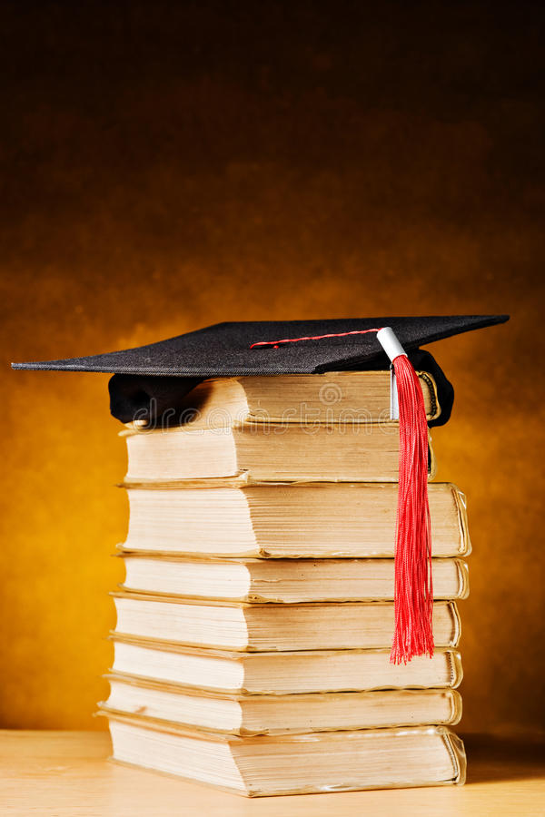 Graduation cap and books. Graduation cap and old books royalty free stock photography