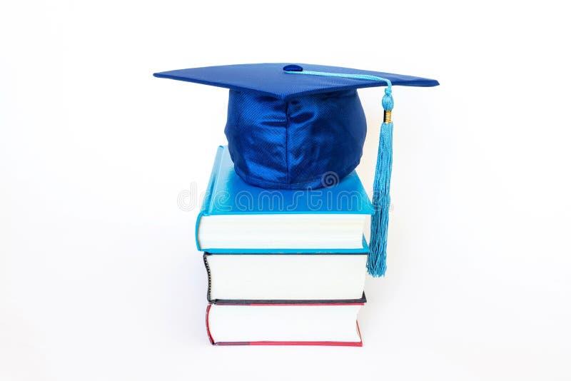 Graduation Cap on Books Isolated on White Background. Blue graduation cap on top of books isolated on white background. Education concept stock image