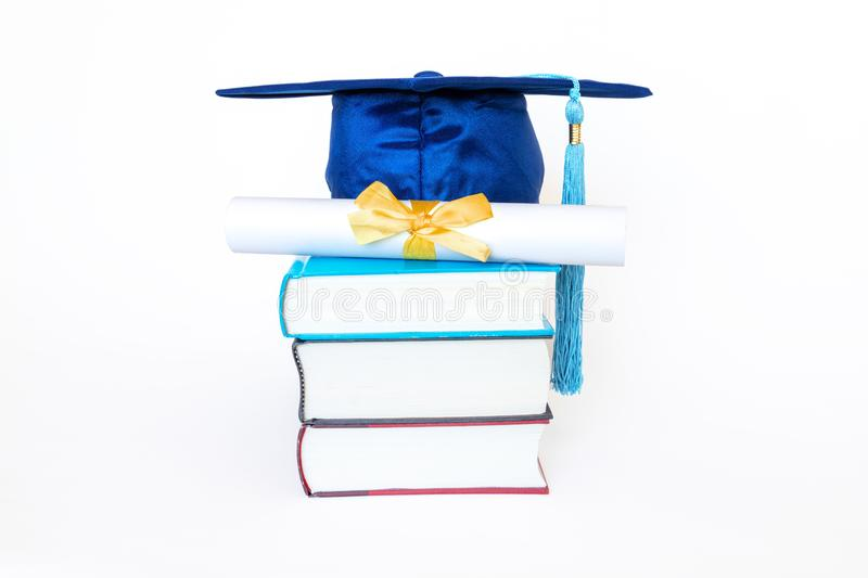 Graduation Cap With Diploma on Books Isolated on White Background. Blue graduation cap with diploma and golden ribbon on top of books isolated on white stock image
