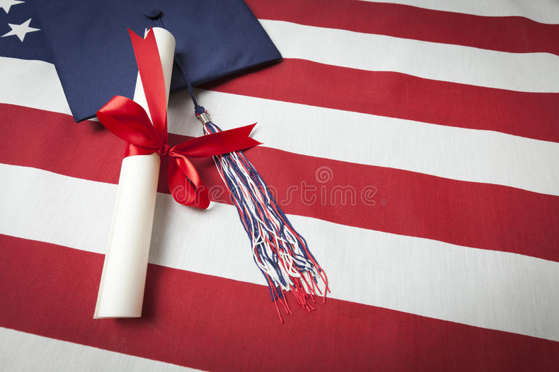 Graduation Cap And Diploma Resting On American Flag Stock