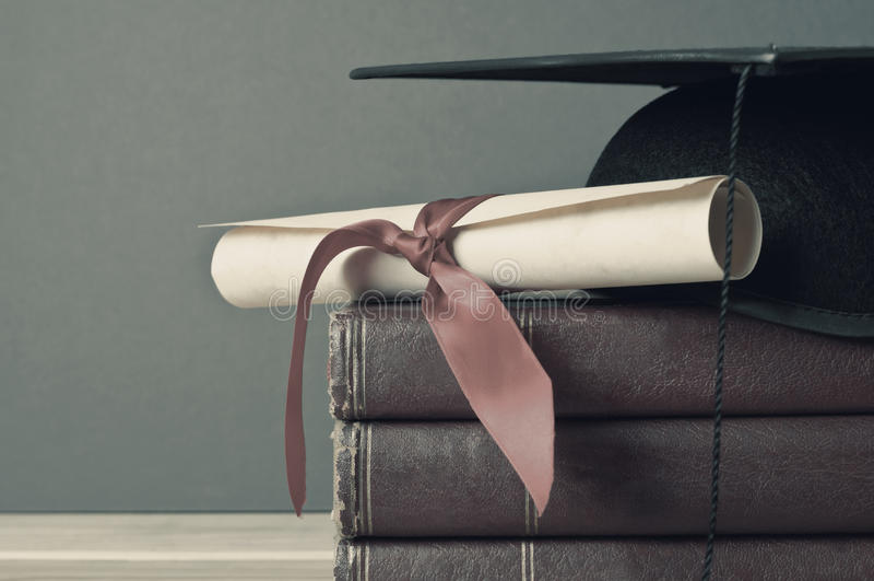Graduation Cap, Scroll and Books - Faded Tones stock photo
