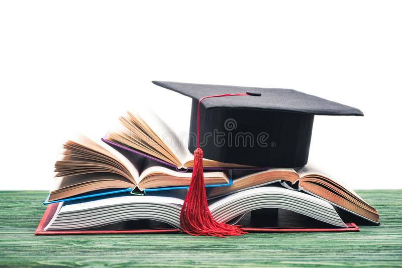 Graduation cap on stack of open books royalty free stock photography