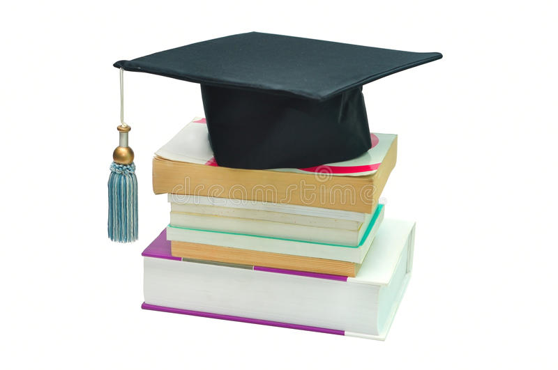Graduation cap on top of a stack of books royalty free stock photos