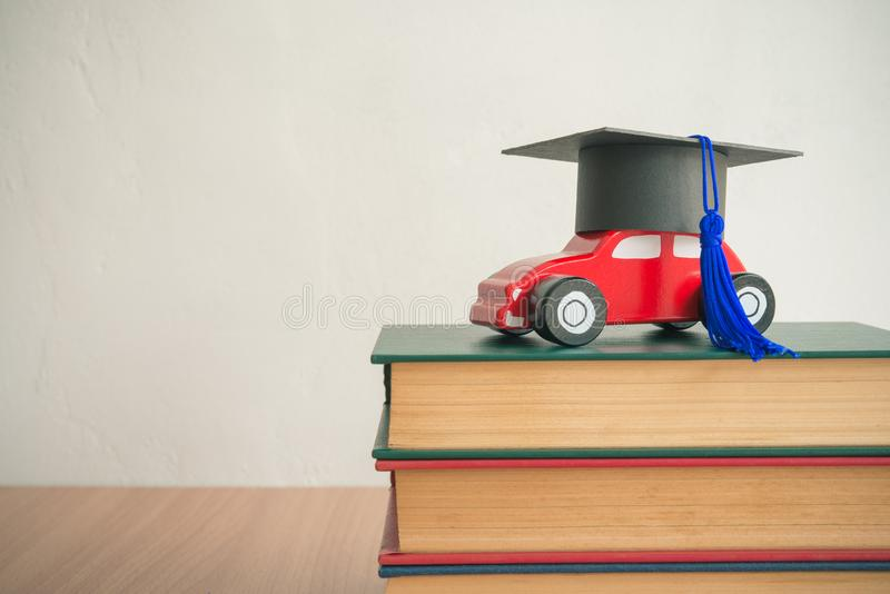 Graduation cap on wooden car over the pile of books on white wall background - Education concept royalty free stock images