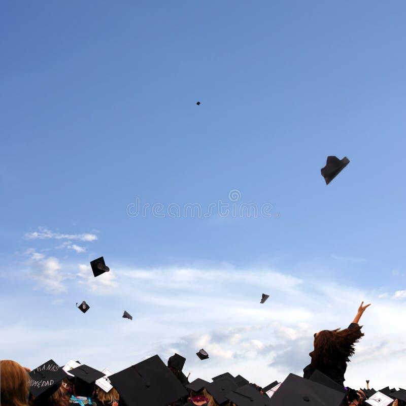 Graduation Celebration. Graduates throwing their caps into air following graduation ceremony, blue sky royalty free stock photos