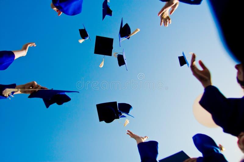 Graduation - chapeaux de vol dans le ciel photographie stock libre de droits