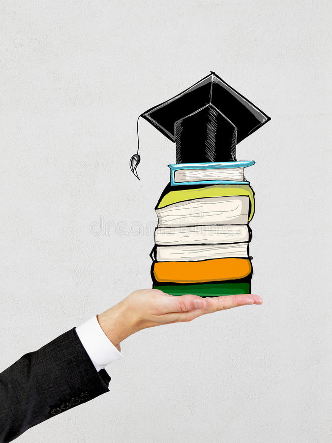 Graduation concept. Businessman hand holding abstract drawing of mortarboard on top of books. Concrete background. Graduation concept stock photo