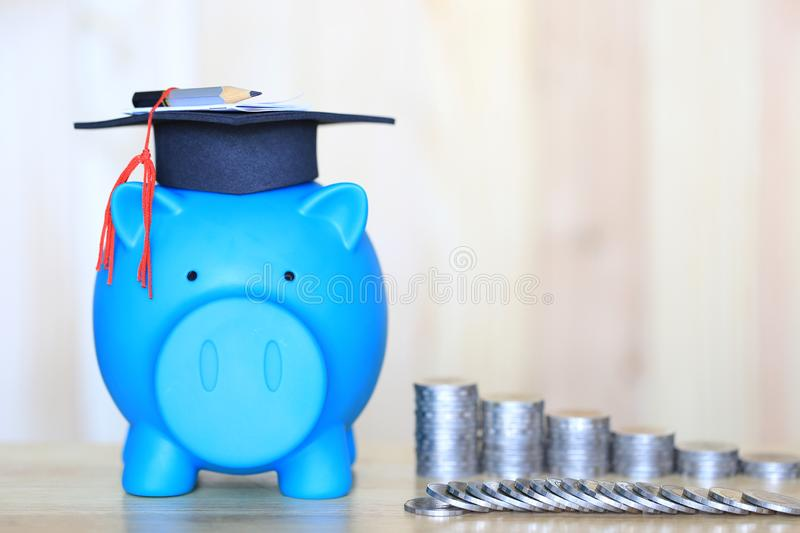 Graduation hat on blue piggy bank with stack of coins money on wooden background, Saving money for education concept stock photography