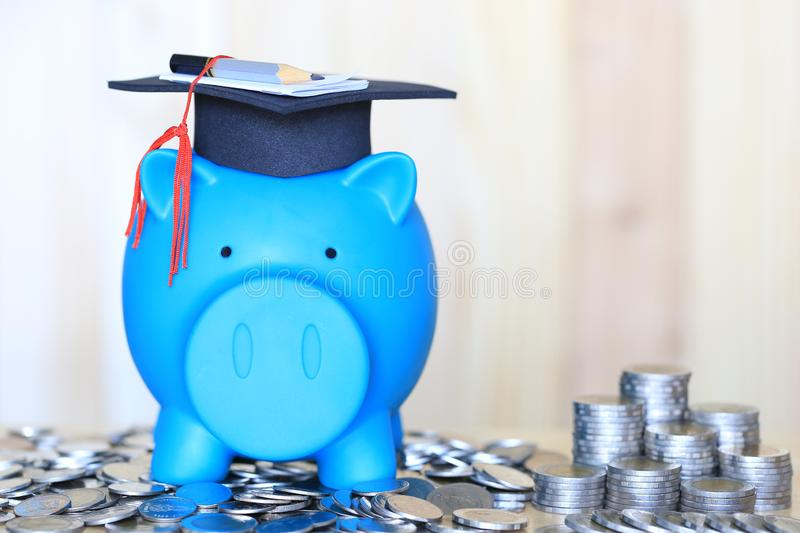 Graduation hat on blue piggy bank with stack of coins money on wooden background, Saving money for education concept. Graduation hat on blue piggy bank with stock photos
