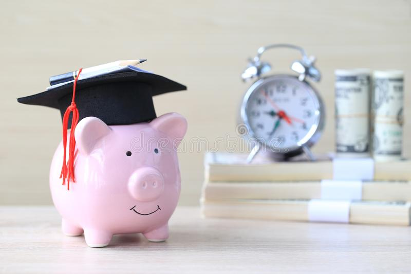 Graduation hat on blue piggy bank with stack of coins money on wooden background, Saving money for education concept.  royalty free stock image
