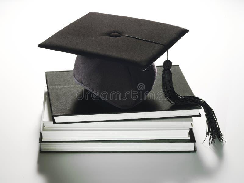 Graduation hat on books stock image