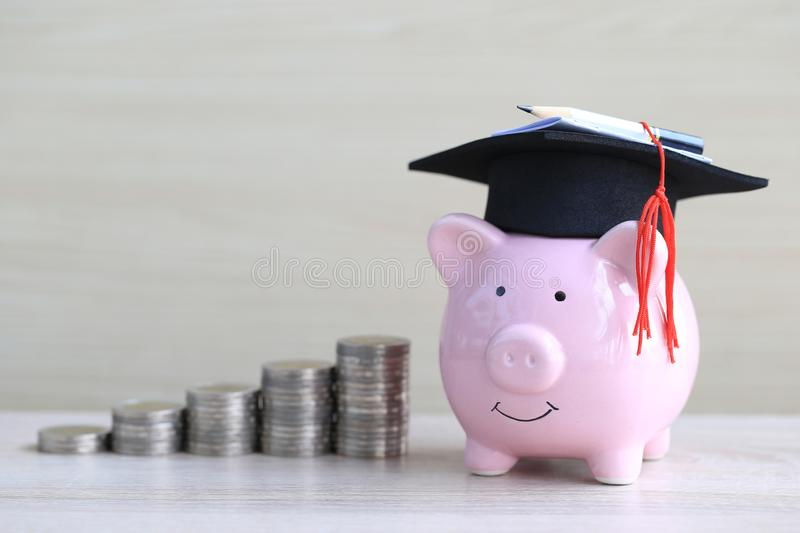 Graduation hat on pink piggy bank with stack of coins money on wooden background, Saving money for education concept stock image