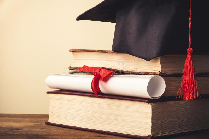 Graduation hat on stack of books and diploma royalty free stock photos
