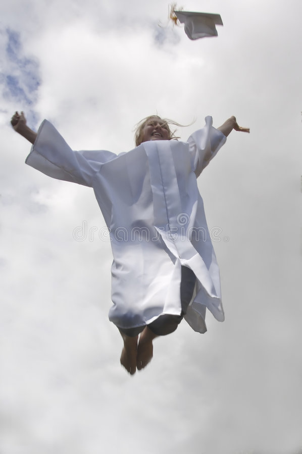 Graduation joy. Girl in graduation gown jumping in the sky and tossing her mortar board royalty free stock photography