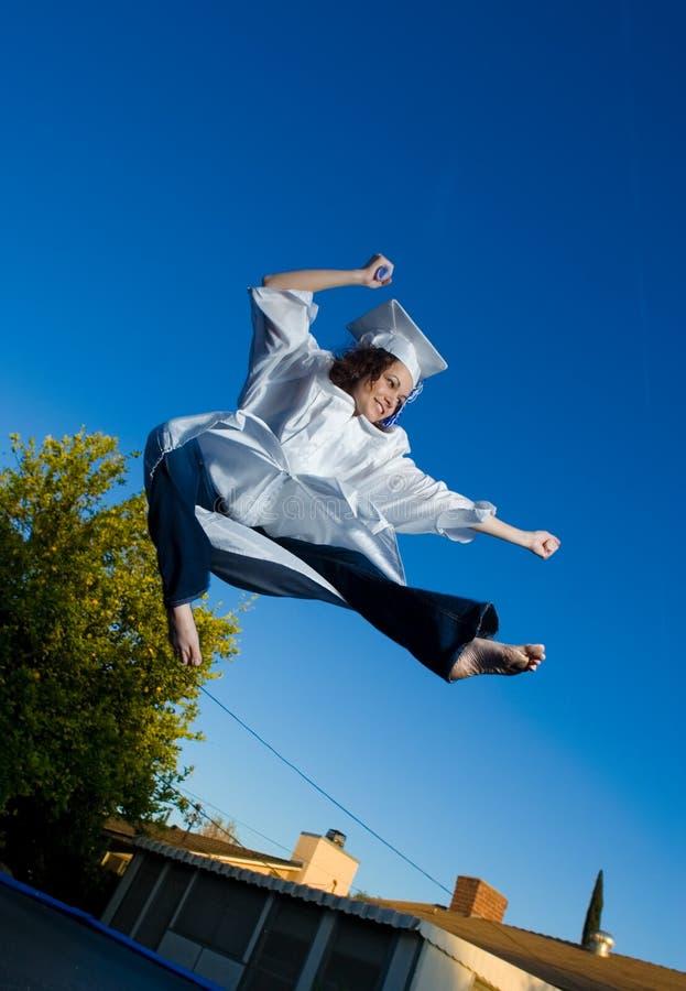 Graduation jump. Happy young graduate doing high jump kick, blue sky behind stock image