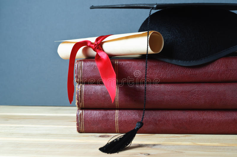 Graduation Mortarboard, Scroll and Books royalty free stock photos