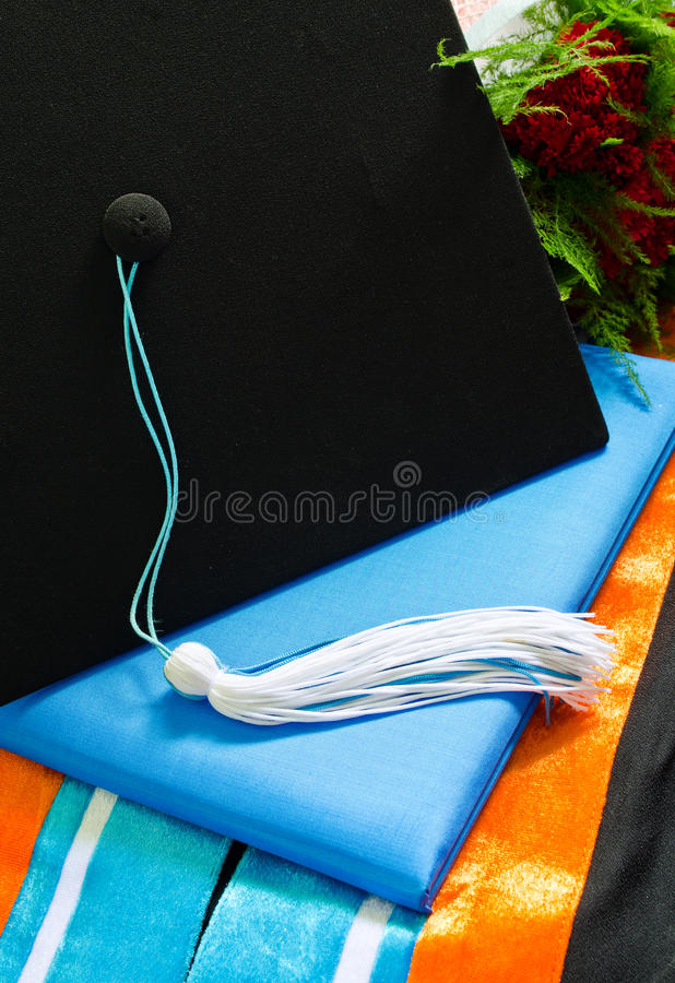 A graduation set with bouquet,cap,tassel, gown, hood and diploma.  stock images