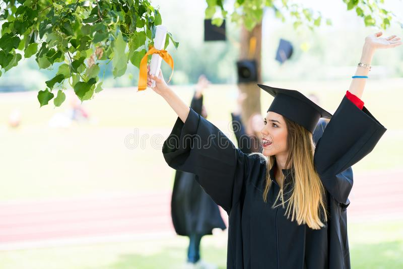 Graduation: Student Standing With Diploma With Friends Behind royalty free stock image