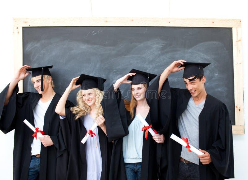 Graduazione del gruppo degli allievi che osservano molto felice fotografia stock libera da diritti