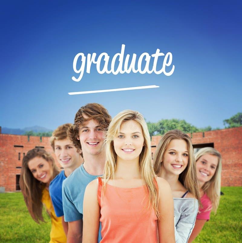 Gradue-se contra os estudantes que usam o portátil no gramado contra a construção da faculdade imagens de stock