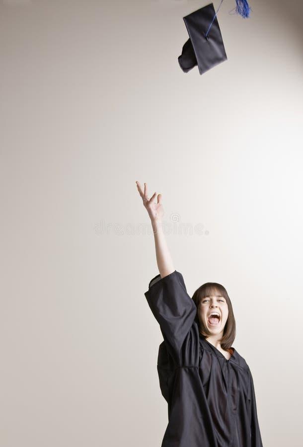 Graduierte werfende Schutzkappe der Frau in die Luft stockfotografie