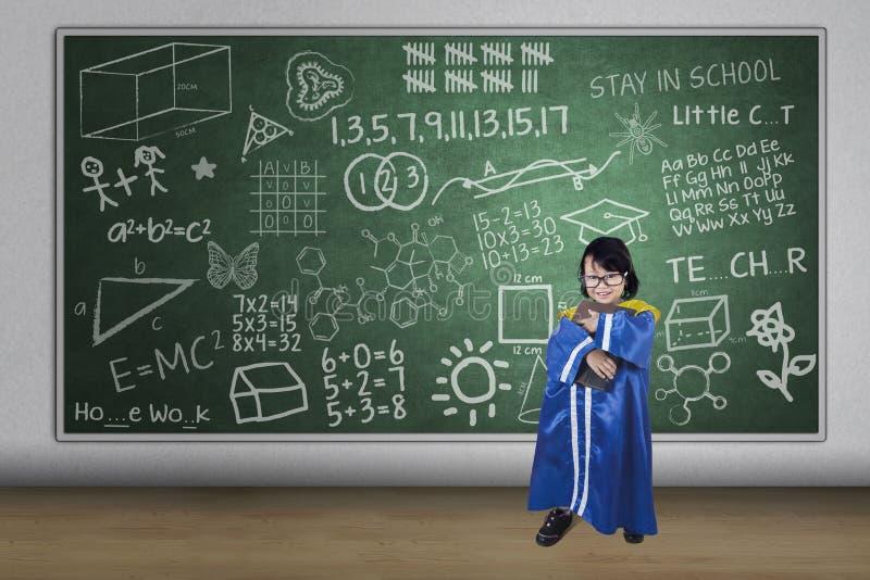 Graduiertes haltenes Buch des asiatischen Mädchens in der Klasse stockfotos