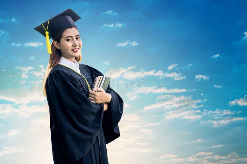 Graduiertes haltenes Buch des Studenten lizenzfreies stockfoto